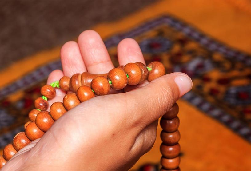 Hand holding religious beads